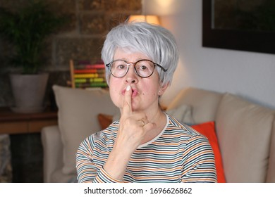 Enigmatic senior woman with finger on lips