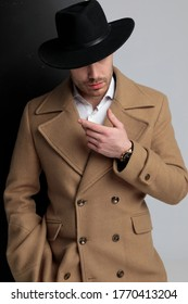 enigmatic young model in long coat wearing hat and pointing finger to side, holding hand in a fashion pose, standing on black grey background
