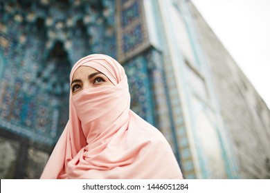 Enigmatic young Muslim lady with brown eyes covering face with hijab and looking into distance while coming in mosque