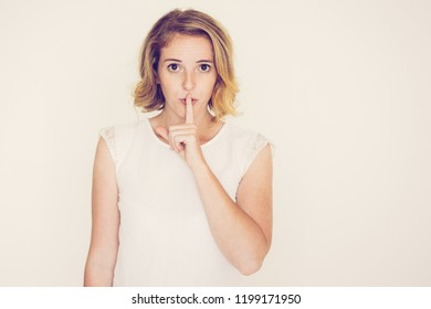 Enigmatic young woman having secret. Pretty serious woman asking to keep quiet. Silence concept