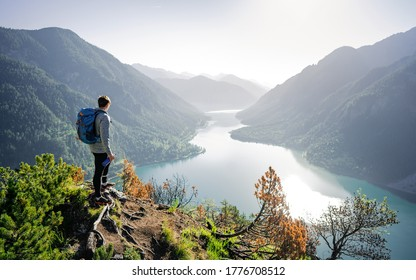 Enjoy the amazing view from top of the world. Hiker take rest for watching the landscape below. Enjoying beautiful view to summer lake with turquoise water