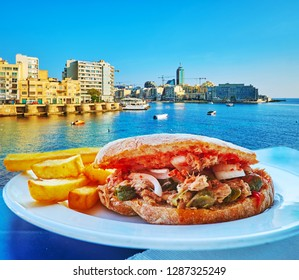 Enjoy delicious tuna sandwich with tomato, capers, sweet onion and French fries in outdoor cafe of Sliema, located at the Exiles Bay, Malta.