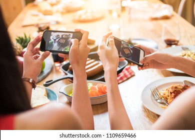 Enjoy dinner eating party with friends and taking photo by phone to post into  social network s, top view of foods on table and group of funny and delicious people