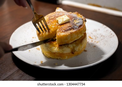 enjoy eating with forkFluffy Japan souffle pancakes, hotcakes with honey syrup and butter light concrete