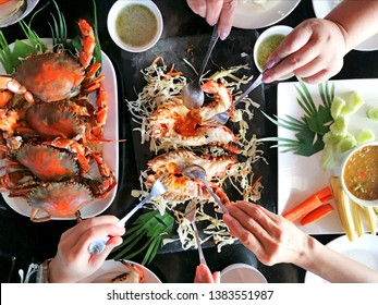 Enjoy eating with friends .Top view of group of people have eating sea food of Thai food, hand holding spoon and fork at Shrimp and Crab fried with spicy sauce , happy time