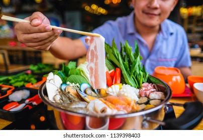 enjoy eating Shabu Shabu and Sukiyaki in hot pot at japanese restaurant.Japanese food are high quality food cooking in hot boil soup with vegetable beef raw meat or pig hold with chopsticks