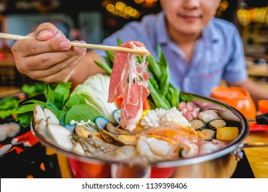 enjoy eating Shabu Shabu and Sukiyaki in hot pot at japanese restaurant.Japanese food are high quality food cooking in hot boil soup with vegetable beef raw meat or seafood hold with chopsticksshabu