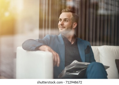 Enjoy every day of your life. Positive self assertive businessman holding a newspaper and sitting on the couch while resting in the office