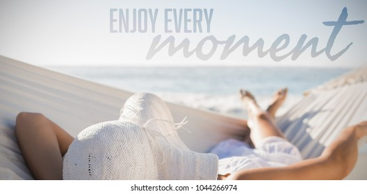 Enjoy every moment against woman in sunhat relaxing on hammock