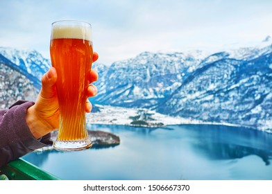 Enjoy the glass of beer in outdoor terrace of the restaurant, located on top of Salzberg mount and observing snowy Alps and Hallstattersee lake, Hallstatt, Salzkammergut, Austria