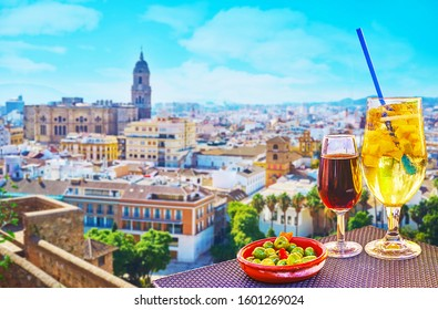 Enjoy the glass of sparkling Cava sangria with fruits or sweet fortified Malaga wine, sitting on the terrace of outdoor restaurant, observing Malaga city with its great Cathedral, Spain