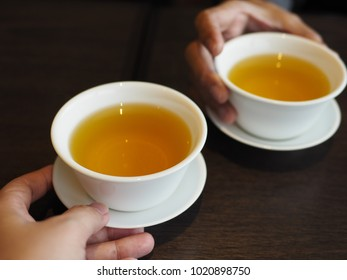 Enjoy healthy tea time with hot flower tea or Chrysanthemum Tea in white cups on dark wooden table. (close-up, selective focus, space for text)