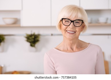 Enjoy home atmosphere. Nice cheerful aged woman smiling and standing in the kitchen