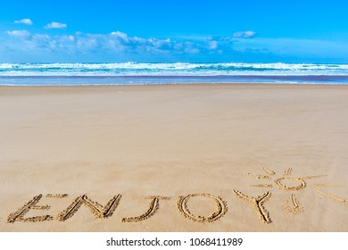 Enjoy inscription on wet beach sand under the sun drawing and sea waves on background. Summer season holiday, vacation concept.