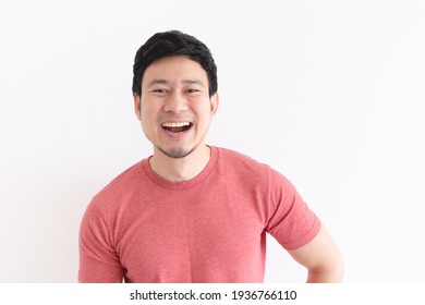 Enjoy and laughing face of Asian man in red t-shirt on isolated background.