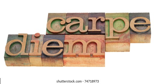 Enjoy life before it is too late, existential cautionary Latin phrase - Carpe Diem  in vintage wood letterpress type, stained by color inks, isolated on white