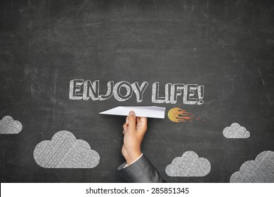 Enjoy life concept on black blackboard with businessman hand holding paper plane