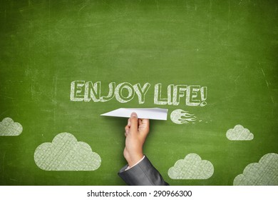 Enjoy life concept on green blackboard with businessman hand holding paper plane
