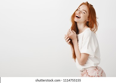 Enjoy life to fullest. Portrait of attractive carefree european female with ginger hair, playing with strands and laughing out loud over gray background, tilting head up, having fun and being amused