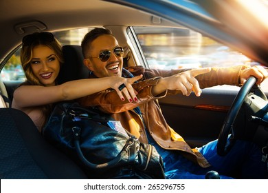 Enjoy life fun couple driving car at high speed and point fingers forward. Inside photo