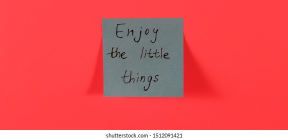 Enjoy the little things. Blue sticky note with inspirational quote on neon pink background. Handwritten positive reminder/advice. Concept for mindfulness and inner peace. Sign of moral support.