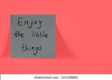 Enjoy the little things. Blue sticky note with inspirational quote on neon pink background. Handwritten positive reminder/advice. Concept for confidence, courage and motivation. Sign of moral support.