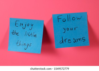 Enjoy the little things. Follow your dreams. Two blue sticky notes with inspirational quotes on neon pink background. Handwritten positive reminder/advice. Sign of moral support.