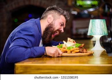Enjoy meal. Cheat meal concept. Hipster hungry eat pub fried food. Manager formal suit sit at bar counter. Delicious meal. Man received meal with fried potato fish sticks meat. High calorie snack.