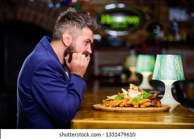 Enjoy meal. High calorie snack. Cheat meal concept. Hipster hungry eat pub fried food. Manager formal suit sit at bar counter. Delicious meal. Man received meal with fried potato fish sticks meat.