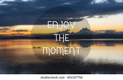Enjoy the moment. Motivation quote on the background of the sea/ocean at the sunset.