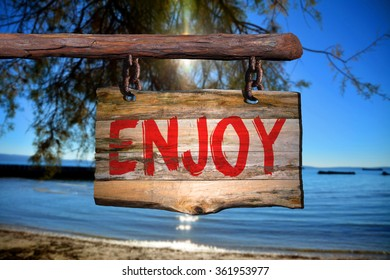 Enjoy motivational phrase sign on old wood with blurred background