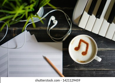 Enjoy Music theme white cup of coffee with musical note symbol on frothy surface flat lay on black painted wood table with keyboard, pencil, blank staff notation sheet, earphones, pot plant / top view