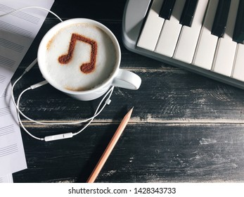 Enjoy Music theme white cup of coffee with musical note symbol on frothy surface flat lay on black painted wood table with keyboard, pencil, blank staff notation sheet, earphones. (selective focus)