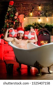 Enjoy New Years Eve celebrations book stay hotel apartment. Christmas tour concept. Man lying in bathtub with gift box. Sexy hedonist relax in bathtub. Stunning winter views enjoyed from bathtub.