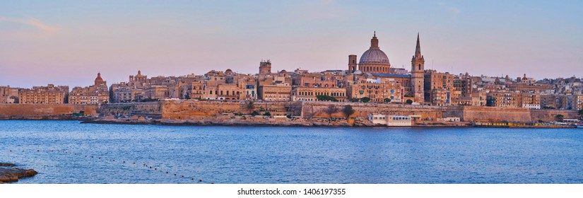 Enjoy the panoramic skyline of medieval Valletta and the purple waters of Northern Harbor from the Tigne Point peninsula of Sliema, Malta