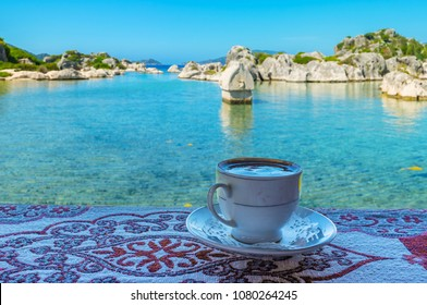 Enjoy refreshing Turkish coffee on the coast of Kekova Bay with a view on ancient Lycian ruins in water, Kalekoy, Turkey.