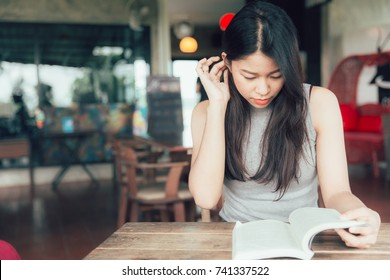 Enjoy relax times with reading books Asian women beautiful Thai teen read a book in coffee shop vintage color tone