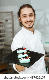 Enjoy! Selective focus on the beautiful glazed cakes on a plate a cheerful professional pastry chef is holding