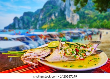 Enjoy the steamed fish with lime and spices in outdoor cafe of Phi Phi Don Island with a view on the beach, Krabi, Thailand