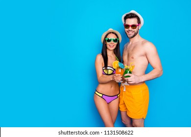 Enjoy the summer! Smiling couple stand in swimsuit, hugging each other and holding summer cocktails with small umbrella. Happy and rest people isolated on blue background with empty place for text