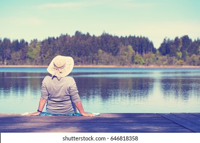enjoy summer time, mature woman sitting on wooden jetty at lake