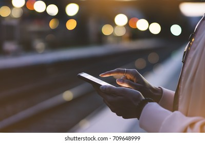 Enjoy travel. Young woman wait on station platform on background light electric moving train using smart phone in night. Tourist text message and plan route of stop railway, railroad transport
