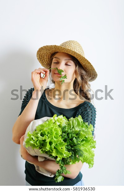 Enjoy young woman with lettuce, celery and parsley in hands. Healthy lifestyle
