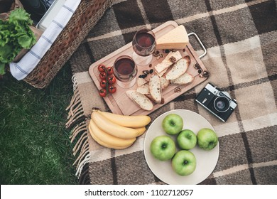 Enjoy your dinner in the nature. Close up top view of organic food and wineglasses on the blanket near picnic basket