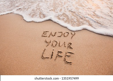 Enjoy your life, happiness concept, positive thinking, inspirational quote written on sand beach.