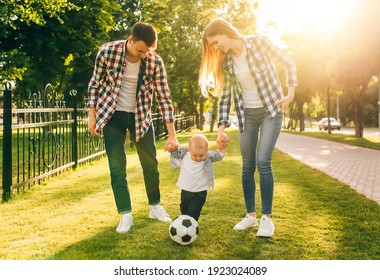 Enjoy your time together. Young happy family, father and mother, hold hands of their little son, walk in the park together with a ball