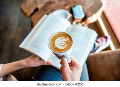 enjoying alone a cappuccino and a book