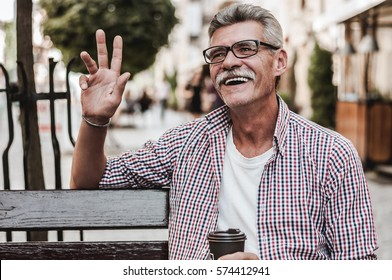 Enjoying a beautiful day. Cheerful mature man sitting on wooden bench with  a cup of coffee and smiling while waving to someone.