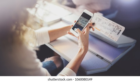 Enjoying business travel concept. Young beautiful brunette tourist girl travelling on the train sitting near the window using smartphone,holding ticket hands