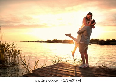 Enjoying By The River.Romantic smiling couple in love dating at sunset at river.